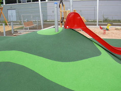 A slide on a playing hill covered with playfix®
